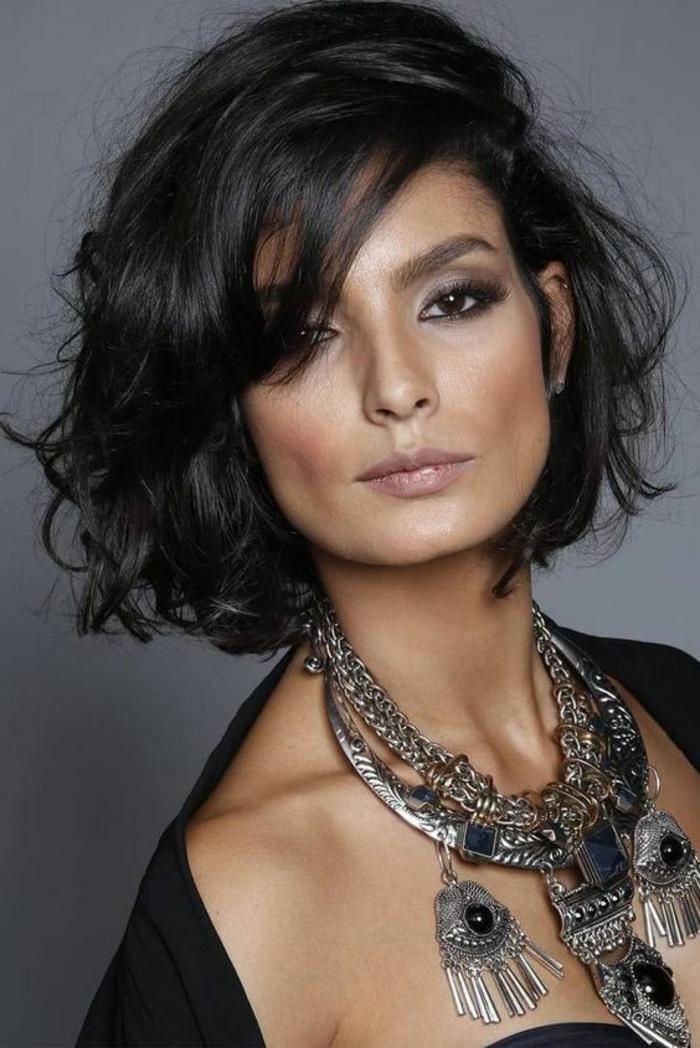 coupe de cheveux femme, bob sur cheveux noir corbeau, front couvert par des mèches latérales, look de séductrice, femme fatale, avec des bijoux massifs au cou