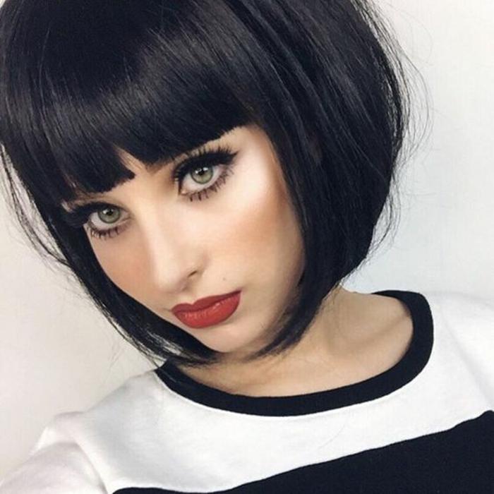 coupe courte femme, cheveux court, couleur noire, visage de femme aux yeux verts et rouge à lèvres couleur brique, chic français