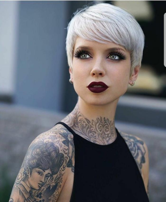 coiffure cheveux court en gris-blanc, avec des mèches qui couvrent le front et les oreilles, look de femme hipster, visage fortement maquillé yeux verts avec des multiples couches de mascara noir, rouge à lèvres en rouge bordeaux intense