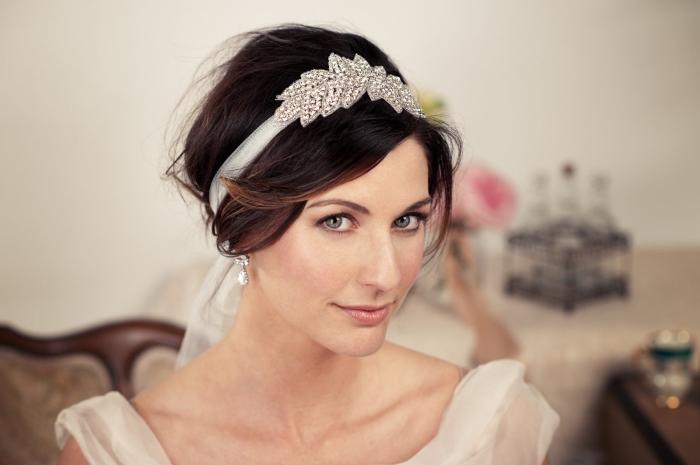 modèle de coiffure de mariée aux cheveux attachés en chignon bas avec frange longue de côté