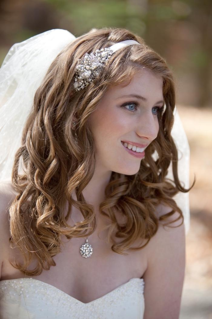 modèle de coiffure de mariée aux cheveux longs et bouclés de nuance châtain foncé avec diadème et voile