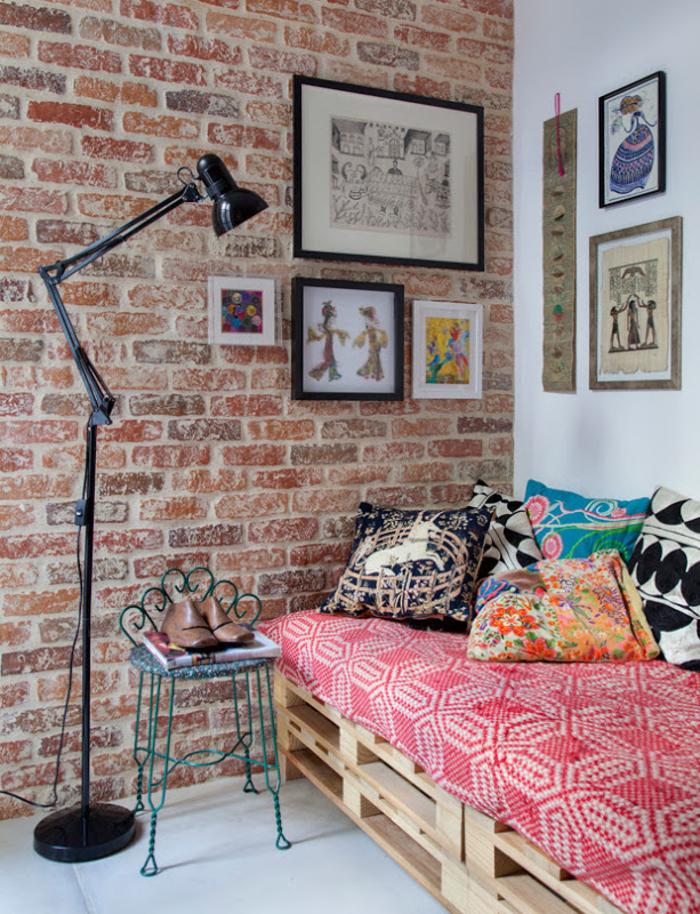 coin repos bohème chic avec canapé en palette posé contre un mur effet brique