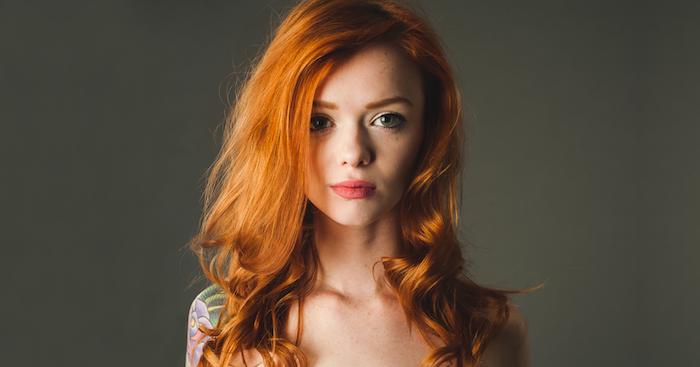 coloration rousse sur des cheveux en dégradé ondulés, peau blanche et des yeux verts, tatouage épaule