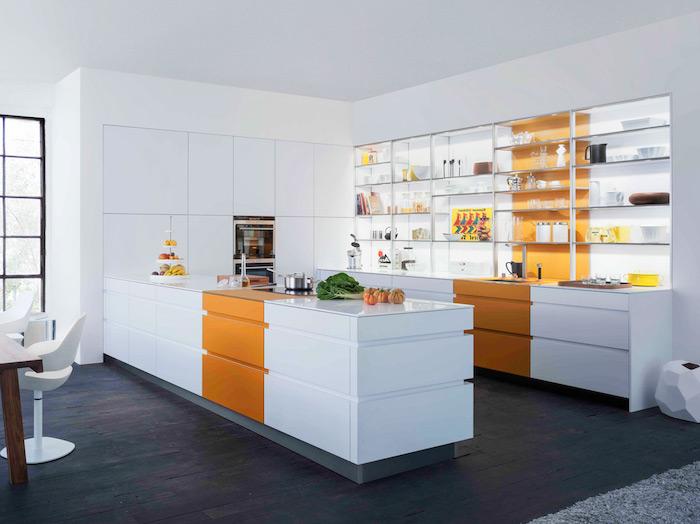 cuisine moderne blanche avec des touches de couleur orange, parquet bois foncé, etageres ouvertes, salle à manger table bois marron et chaises design