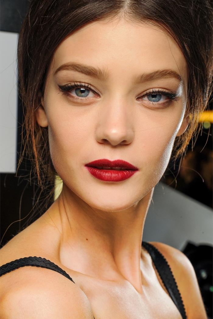 comment se maquiller les yeux, femme aux cheveux attachés en chignon et maquillage en lèvres rouge