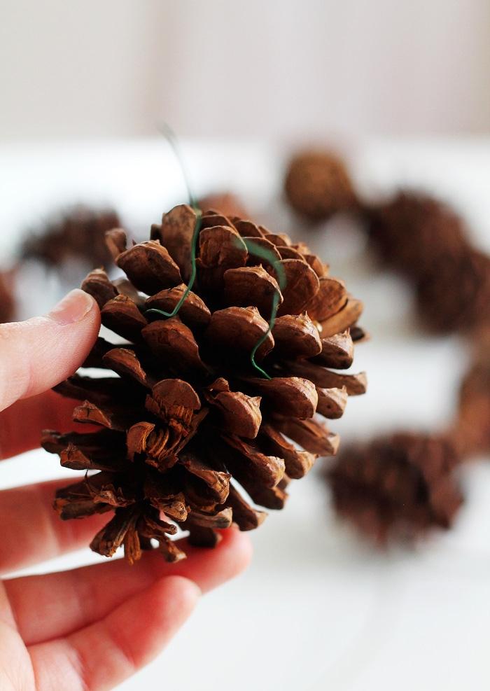 un projet diy noel pour avec des pommes de pin, couronne de noël naturelle réalisée avec des pommes de pin et un cintre