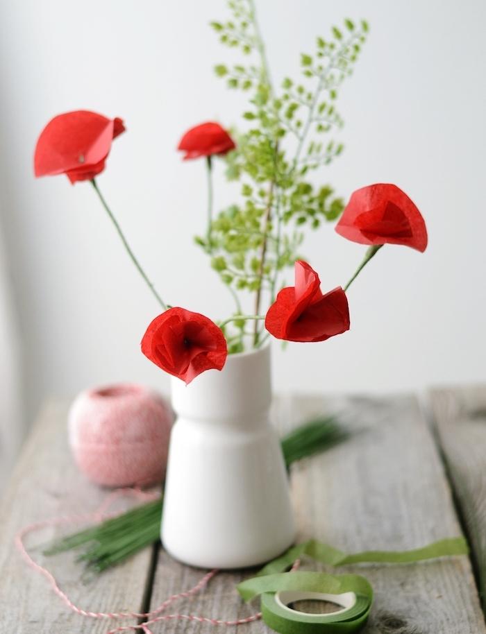 modele de coquelicot rouge avec des tiges en fil de fer vert et pétales rouges dans un vase en verre blanc