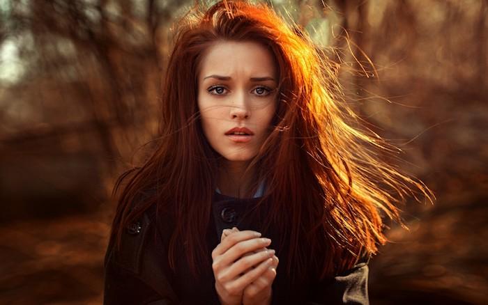 tie and dye roux, cheveux couleur chatain cuivré sur une chevelure longue, manteau noir et des yeux bleus