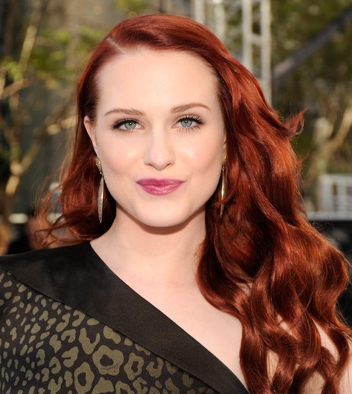 idée de cheveux auburn couleur rouge foncée aux éclats roux, frange et cheveux longs ondulés, look tapis rouge, robe noire stylée