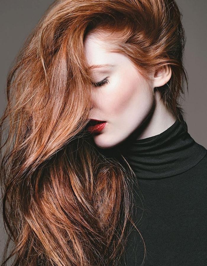 couleur de cheveux chatain cuivré, cheveux sur le coté avec du volume, pull avec col noir, rouge à lèvres rouge