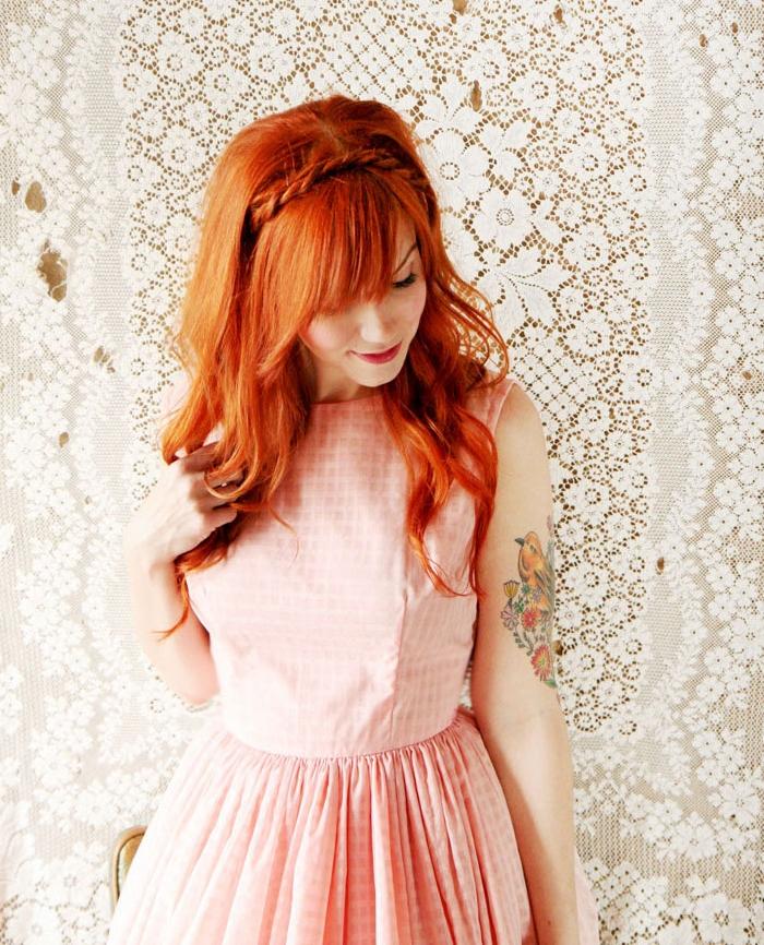 cheveux couleur cuivrée longs bouclés, coiffure avec tresse et frange asymetique, ribe vintage rose