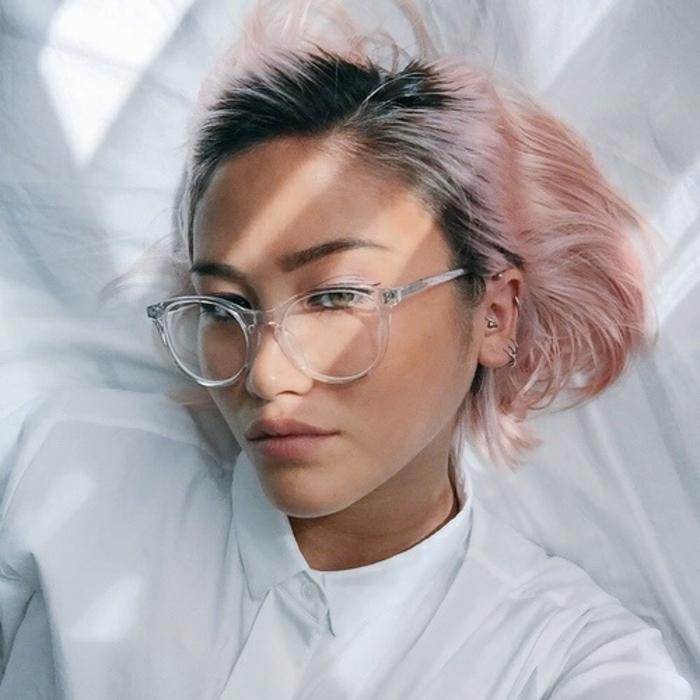 coupe courte femme, cheveux en rose acidulé, racines noires, sourcils épais teints en noir, lèvres maquillées discrètement, grandes lunettes blanches transparentes