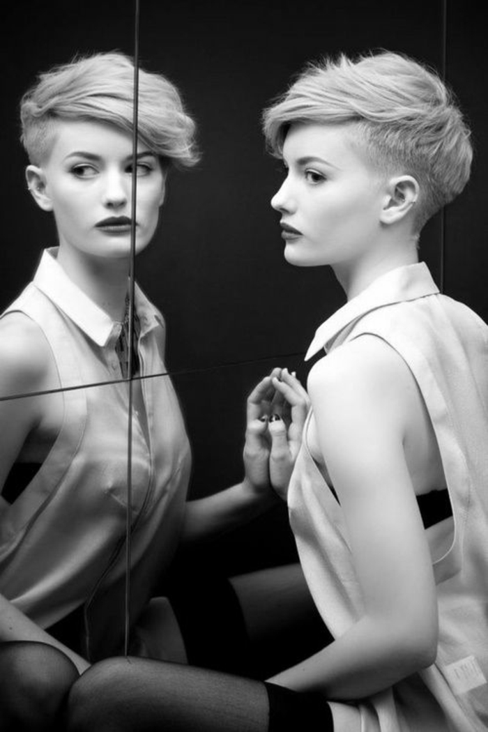 coupe courte femme, pixie blond, femme en tenue sexy, chemisette blanche semi-transparente sans manches, mèches devant qui couvrent partiellement le front de côté