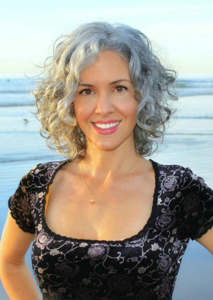 coupe de cheveux femme en nuances grises, toute en grandes boucles, longueurs sous le menton, coiffure sans frange, raie de côté