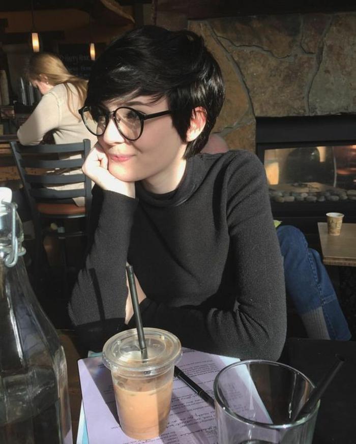 coupe de cheveux femme, pixie court avec cheveux en châtain foncé, fille cool et chic avec des grandes lunettes rondes en noir