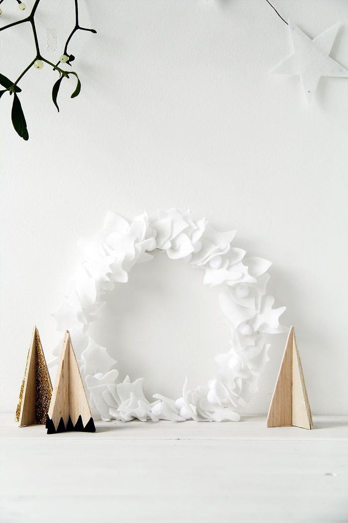 idée pour une deco noel a faire soi meme de style scandinave, couronne de noel en feuilles de feutrine blanches qui s'inscrit bien dans l'ambiance épurée scandinave