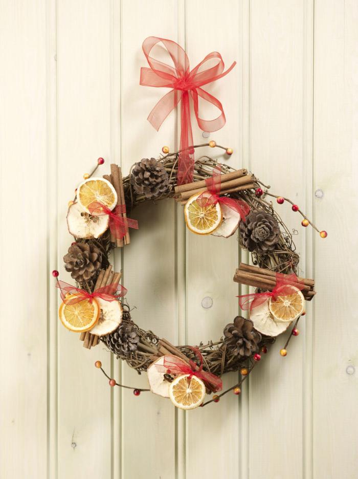 jolie couronne de noel a faire soi meme en branchage, fruits séchés, bâtons de cannelle et ruban en organza