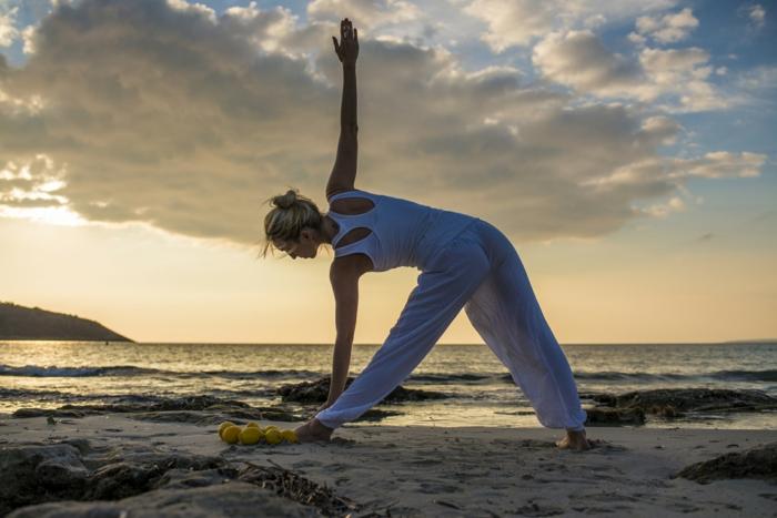 cours de yoga, tenue de yoga blanche, pratique physique et spirituelle, faire du yoga sur la plage