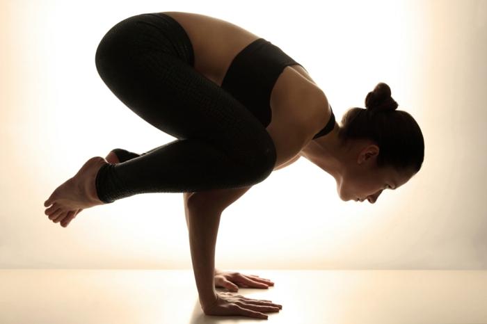 cours de yoga, posture corbeau exécutée par une femme, force et sérénité