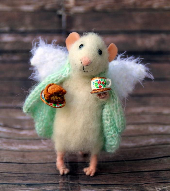 créer des sculptures en laine, une souris blanche amusante qui tient une tasse de café et un morceau de gateau