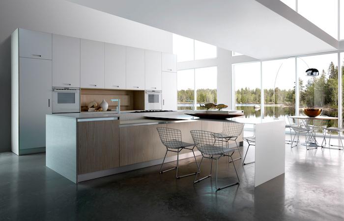 cuisine equipee-avec meubles blancs et credence bois, ilot central blanc et bois, sol gris anthracite, chaises metalliques, grandes fenetres