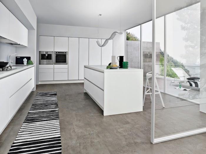 cuisine equipee avec meuble cuisine et ilot central blanc, sol carrelage gris, tapis noir et blanc, electromenager inox, verriere blanche