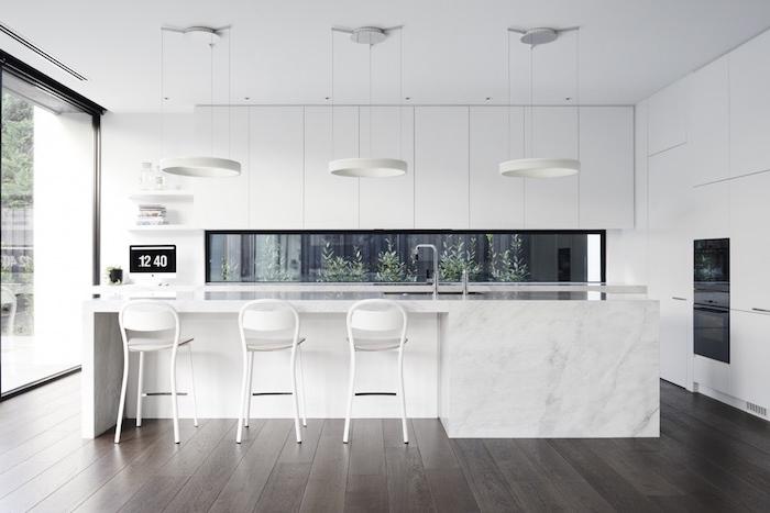 cuisine moderne blanche, design scandinave, meuble cuisine et ilot central blanc, parquet marron, suspensions originales