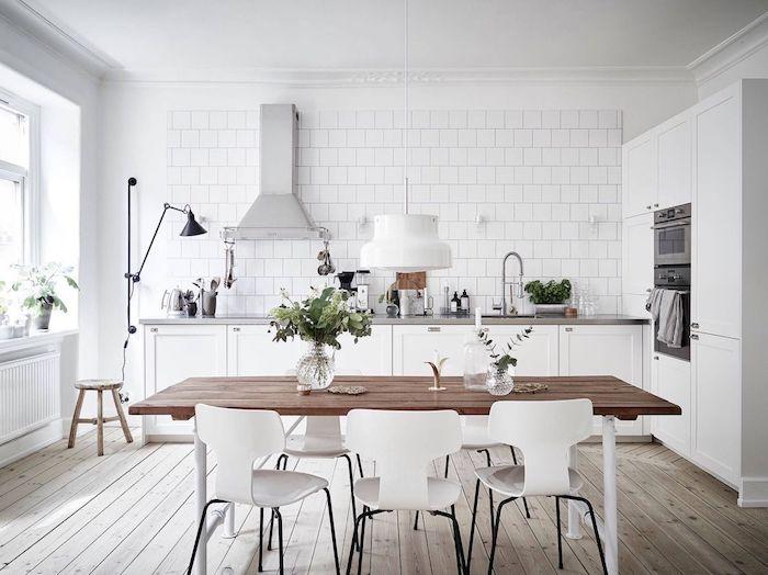 cuisine equipee en blanc avec une plan de travail gris, carrelage blanc, parquet clair, chaises blanches, aspirateur inox, style scandinave
