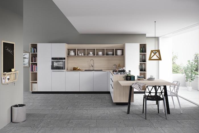 modele de cuisine amenage en blanc avec credence bois, table bois et chaises metal, revetement sol dalles en beton, murs gris