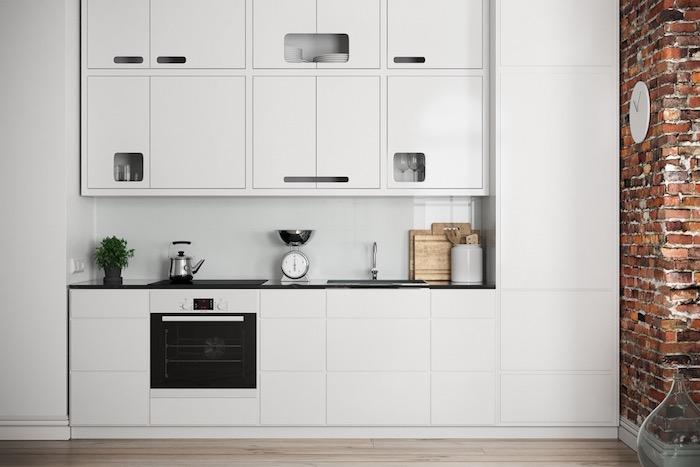 cuisine blanc laqué tout en blanc avec un four noir contrastant, mur en briques et parquet bois clair, design moderne industriel