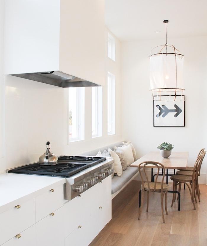 exemple de cuisine amenage en blanc et bois avec facade cuisine blanche et coin repas adjacent avec canapé, table et chaises en bois