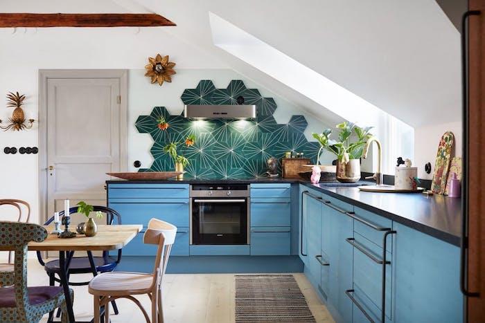 cuisine amenagee en angle, meubles cuisine bleus, carrelage vert, modele de cuisine sous pente, table bois et metal et chaises vintage bois