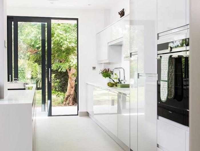 cuisine moderne blanche, meubles cuisine finition brillante laquée, porte vitrée avec encadrement noir, four noir