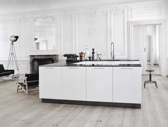 cuisine equipee blanche avec ilot central blanc, doté de plan de travail noir, murs décorés de moulures blanches, cheminée vintage baroque, parquet bois clair
