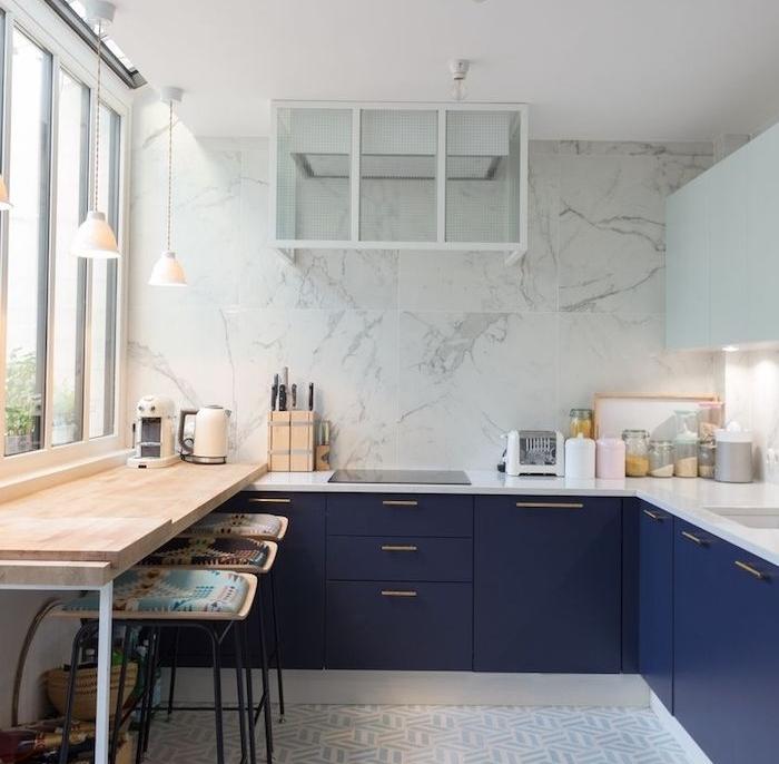 modele de cuisine angle avec meuble bas bleu marine et plan de travail blanc, credence cuisine et mur en marbre, petit bar avec tabourets noirs, revêtus de coussins colorés