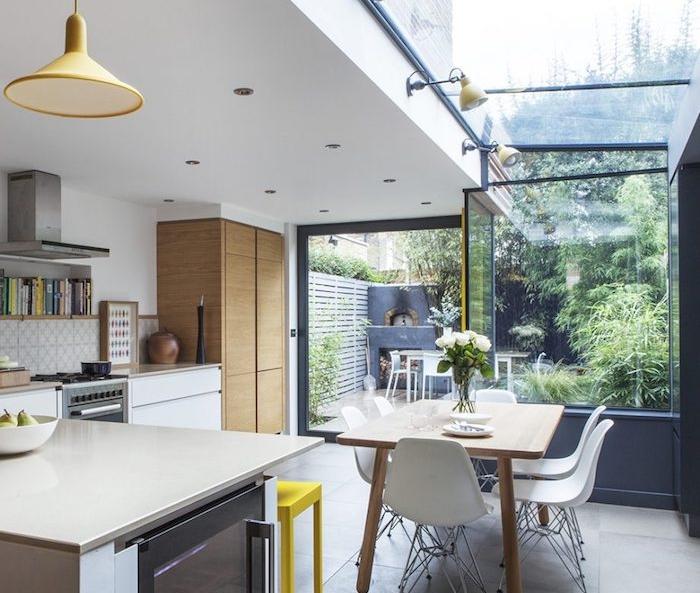 cuisine en l moderne avec meubles bas blancs retro, plan de travail beige, etagere avec livres de cuisine, suspension jaune, table salle à manger en bois et chaises blanches