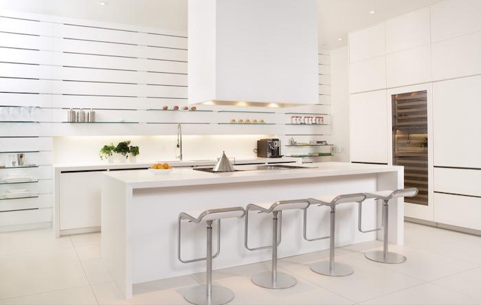 exemple de cuisine avec ilot central blanc et meubles bas blancs, multiples etageres ouvertes en verre, meuble colonne cuisine, chaises inox