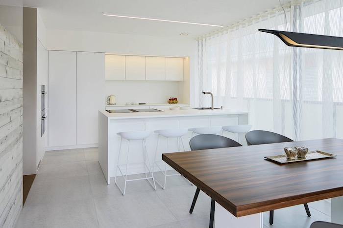 modele de cuisine blanc laqué avec ilot central entouré de chaises blanches design, sol carrelage gris, table bois et chaises noires, eclairage credence integre