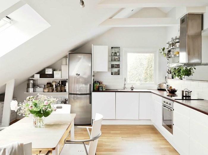 amenagement cuisine angle avec meubles de cuisine blancs et plan de travail marron, parquet clair, table en bois et chaises blanches, electromenager inox