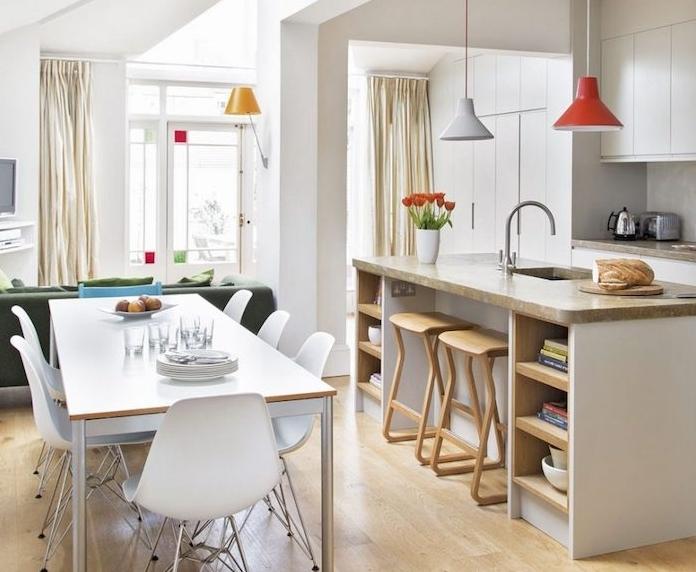 cuisine amenage avec meuble blanc, ilot central avec plan de travail gris, parquet clair, petite salle à manger en table et chaises scandinaves
