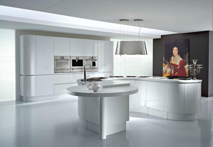 exemple de cuisine blanche laquée avec ilot central en s, mur d accent gris anthracite avec cadre tableau portrait femme vintage, suspension inox design