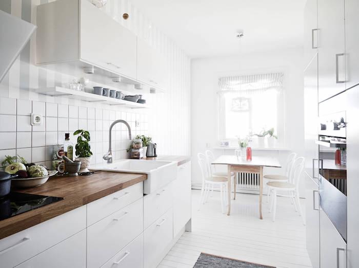 cuisine amenage, idée de meuble cuisine blanc et plan de travail bois foncé, credence carrelage blanc, parquet blanchi, petit coin repas scandinave