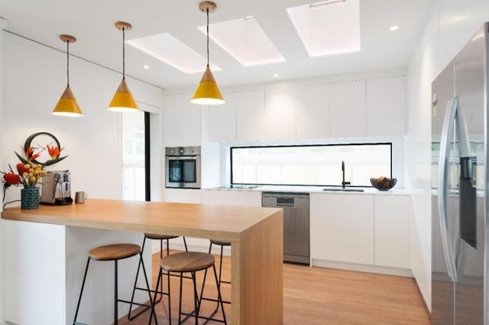 cusiine bois et blanc avec facade cuisine blanche et bar en bois entouré de tabourets en bois et metal, suspensions jaunes design