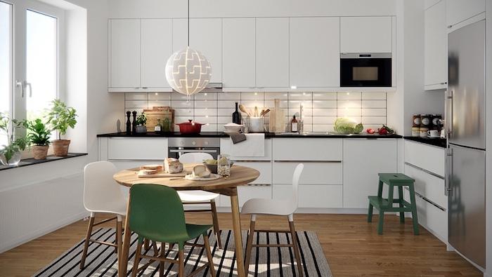 cuisine laquée blanche avec meubles hauts et bas blancs, aprquet bois marron, table bois entourée de chaises blanches et verte, tapis gris et noir, suspension boule lumineuse