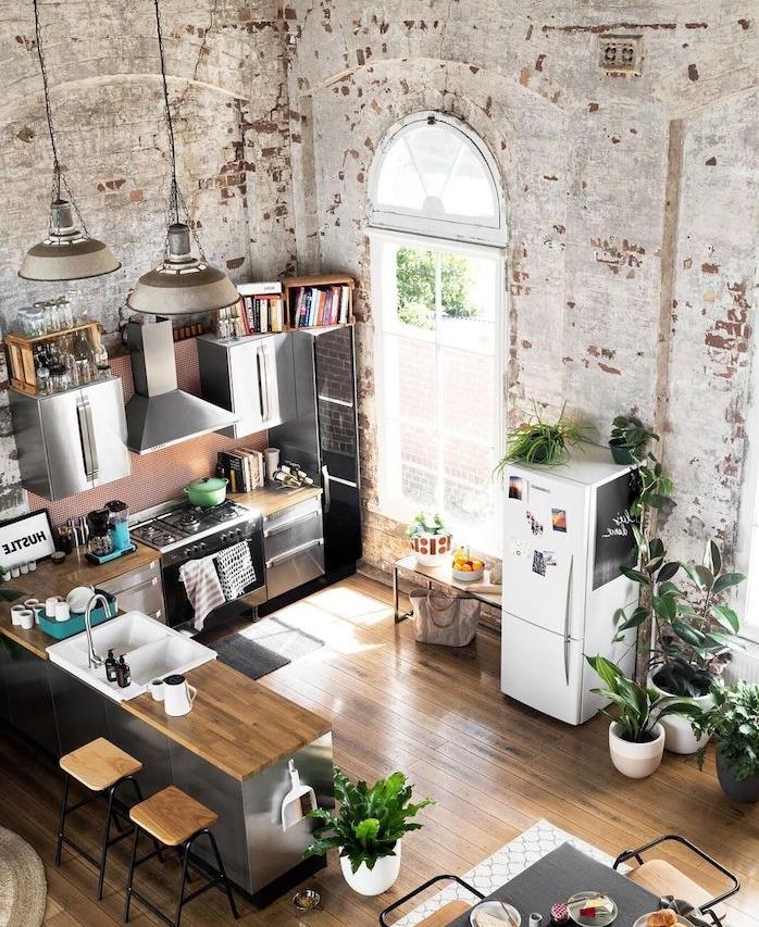 amenagement cuisine en l en inox et bois avec electromenager inox, murs en briques usés, parquet marron clair, suspensions industrielles, cuisine industrielle