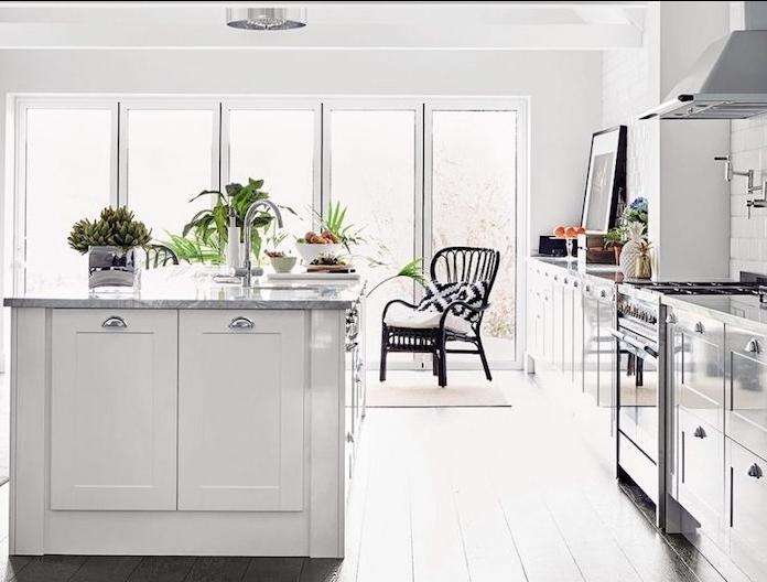 cuisine blanche laquée avec meubles et ilot central blanc doté de plan de travail marbre, parquet blanchi, mut habillé de carrelage blanc, touches de plantes vertes