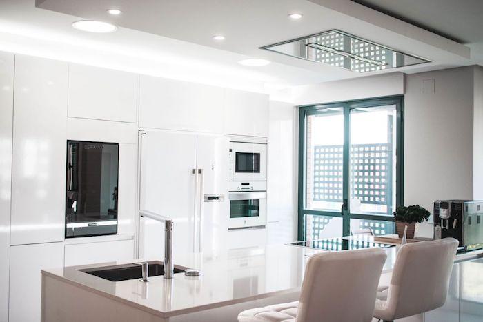 exemple de cuisine laquée blanche, meuble de cuisine blanc, ilot central gris et chaises grises, porte à encadrement vert