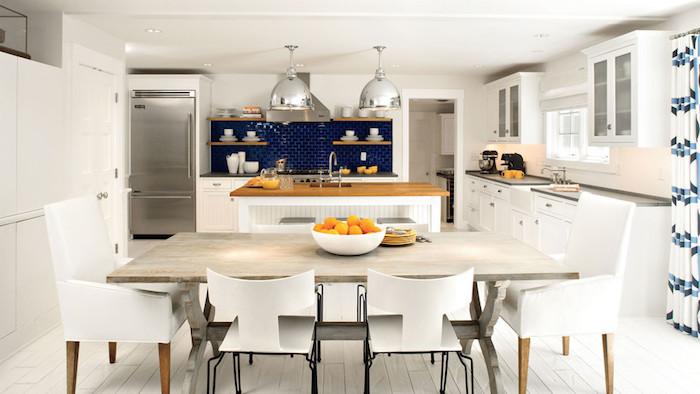 credence cuisine moderne en carrelage bleu marine, bar blanc avec plan de travail bois, table bois grisatre et chaises blanches, parquet blanc, suspensions grises metalliques