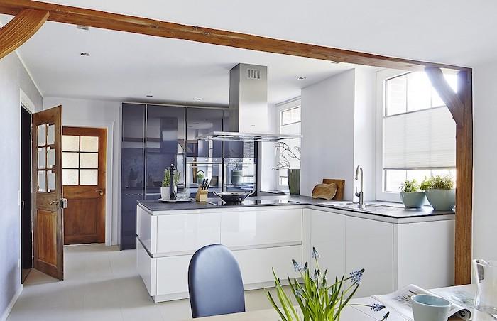 exemple de cuisine blanche et grise moderne, ilot central en l blanc, meuble cuisine gris finition brillante, aspirateur inox, poutres apparentes