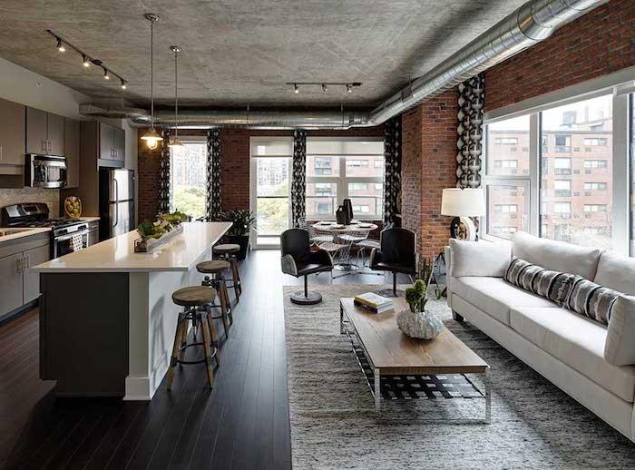deco industrielle dans in salon avec canapé blanc, table basse em bois et metal, plafond effet beton, mur en briques, tuyauterie avec cuisine adjacente